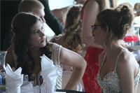 two girls sit and talk at prom event