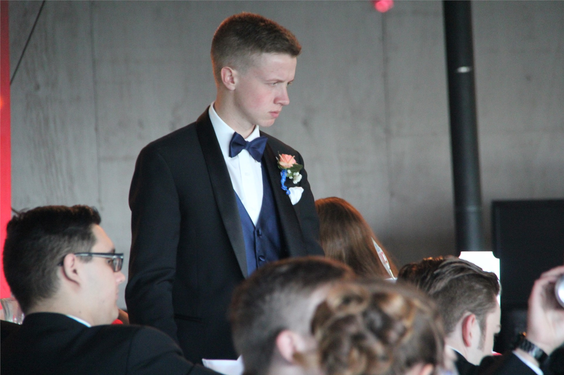 male standing inside prom venue
