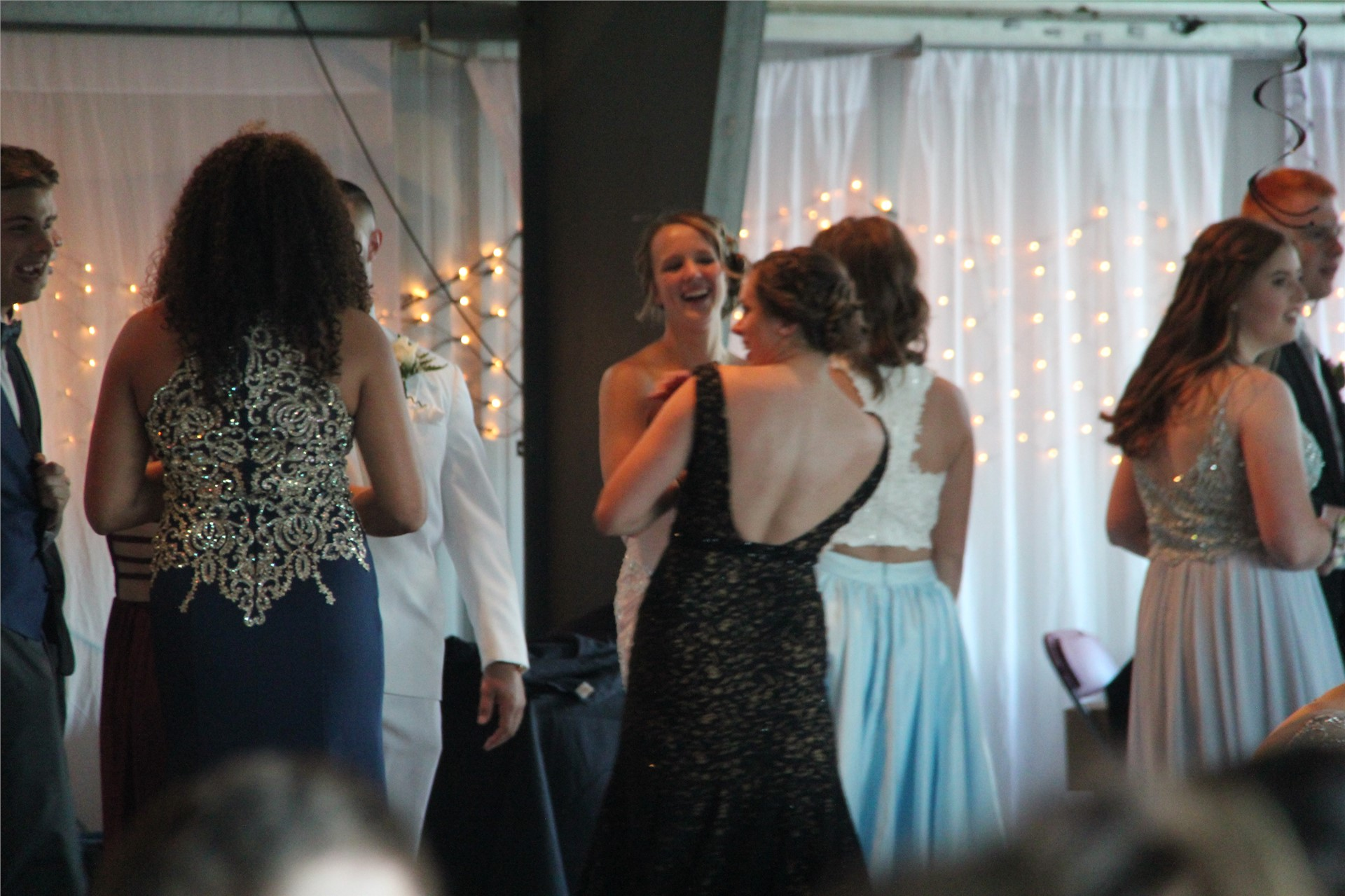 far shot of students socializing inside prom venue