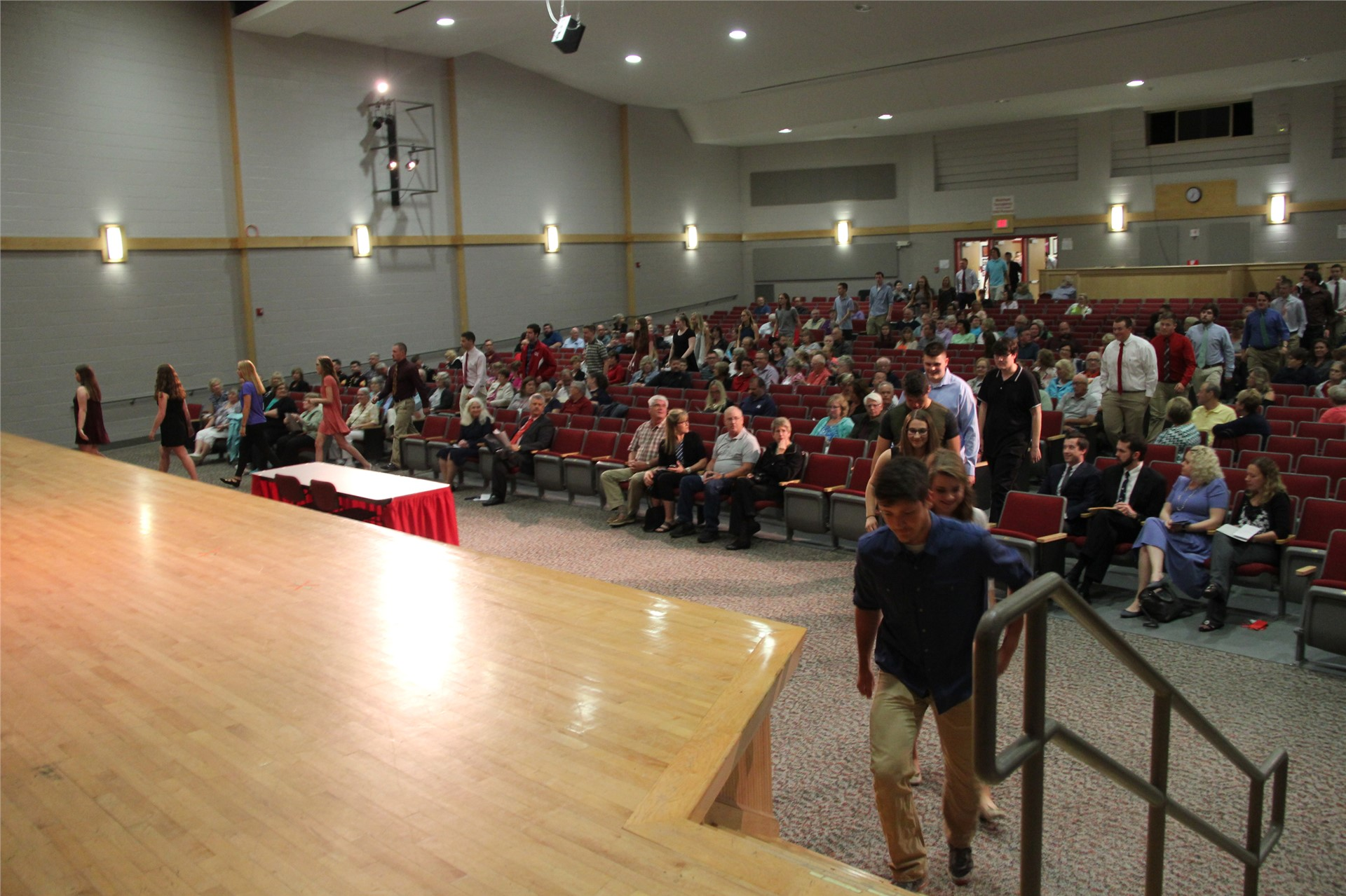 students walk onto auditorium stage