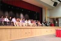 students sit in chairs on stage at awards ceremony from audience point of view