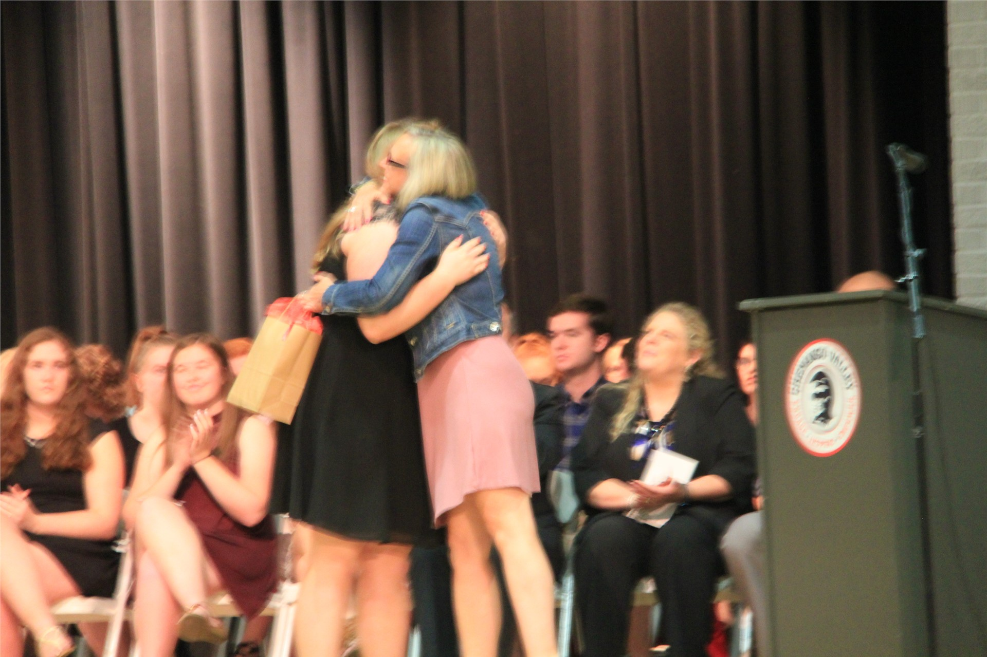 female student hugs woman giving her award