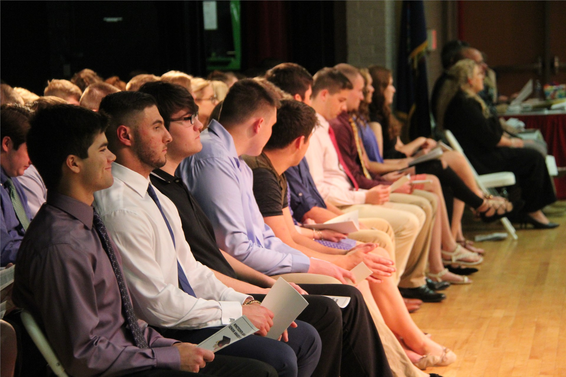 students sit in chairs on stage at awards ceremony