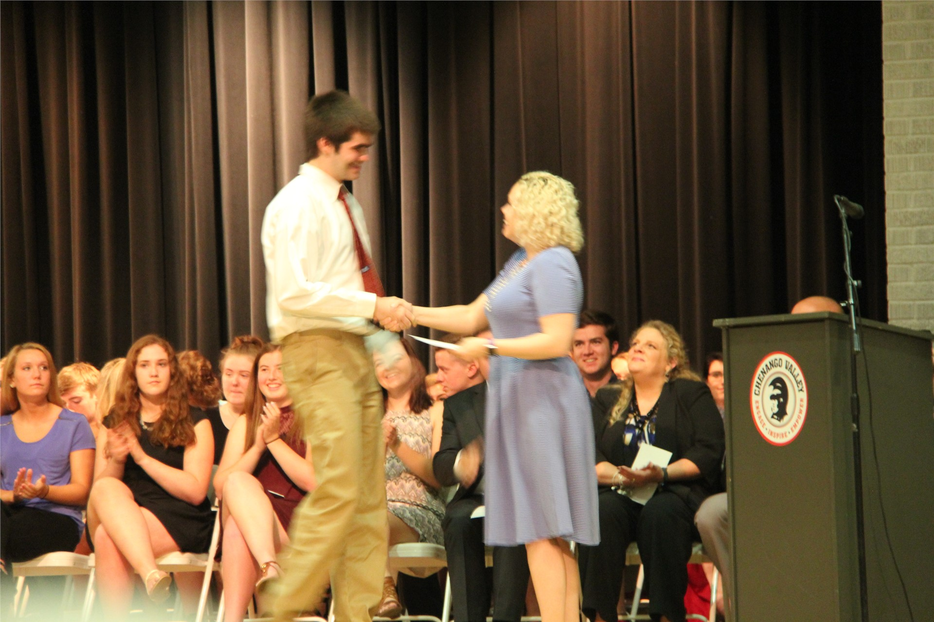 male student accepts award from woman