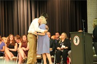 male student hugs woman giving him award