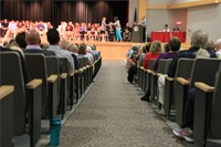 farther away shot students sit on stage at awards ceremony