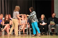 male student accepts award from woman on stage