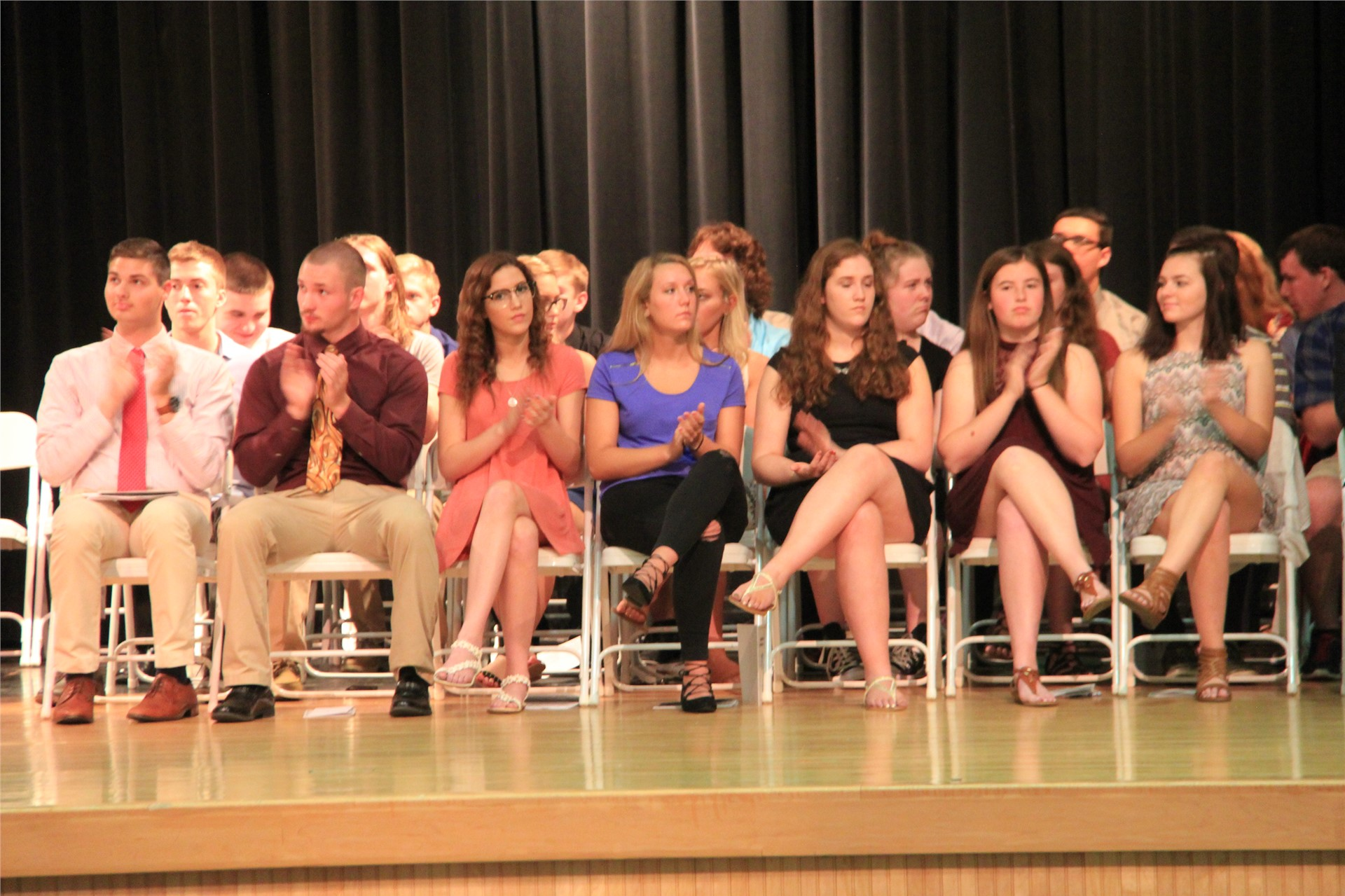 students sitting on stage clap for students receiving awards