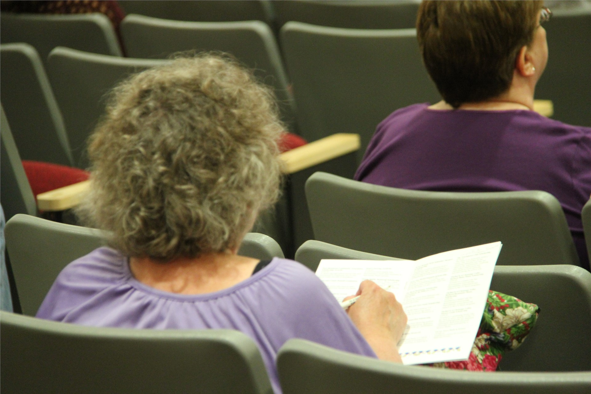 woman in audience holds awards pamphlet in hands