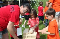 teacher helps students play giant jenga