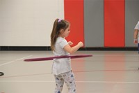 young girl hula hoops in gym