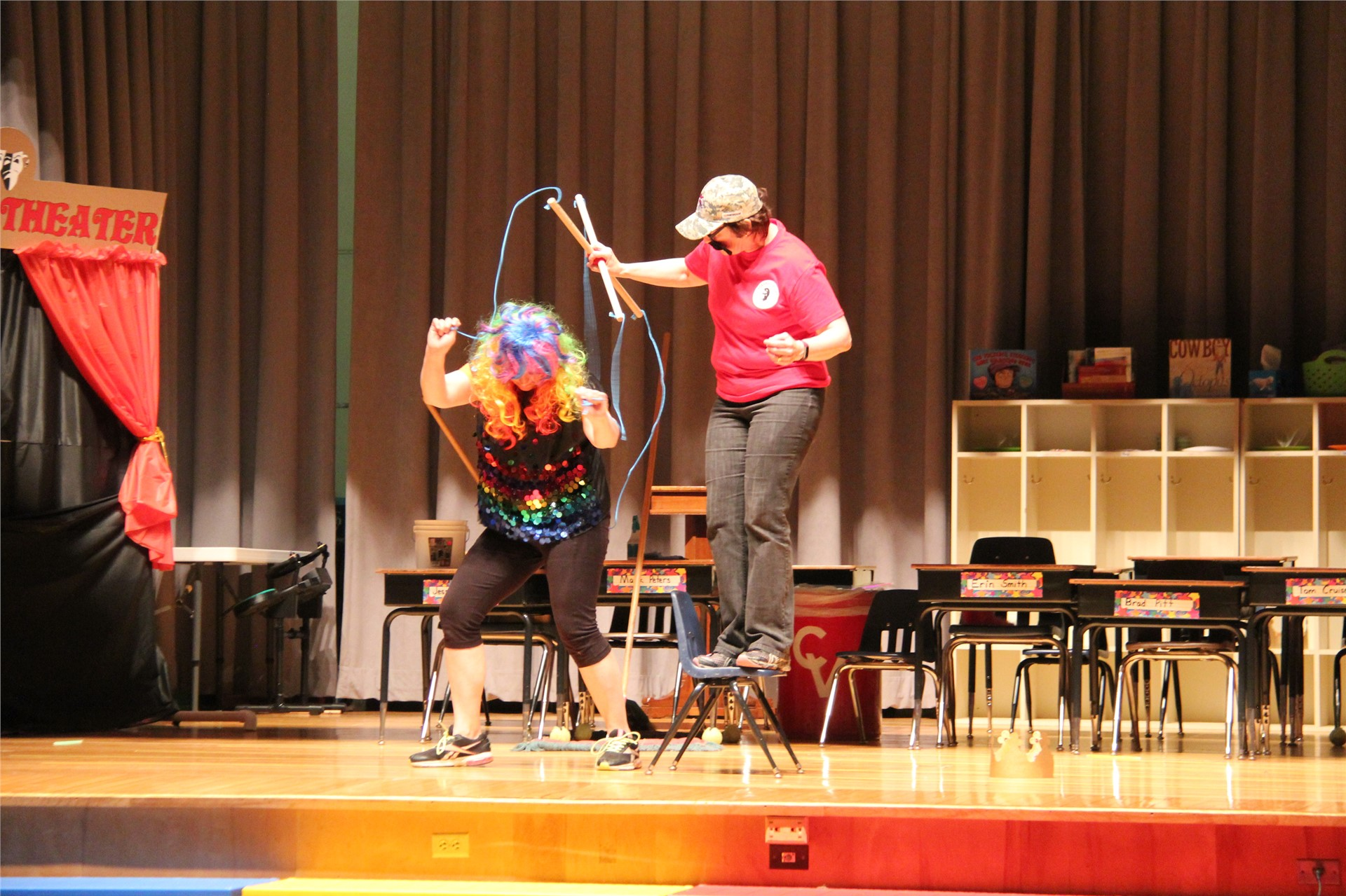 teacher dressed as custodian controls strings of teacher dressed as puppet on stage in talent show