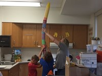 summer steam students help teacher stack cups