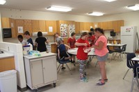 wide shot of students and teachers making pancakes as part of c v summer steam program lesson