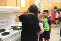 teacher helps students cook pancakes