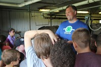 students ask owner question inside of cow barn