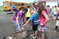 three students pet goat in pen.