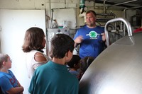 owner talks to students in milk house