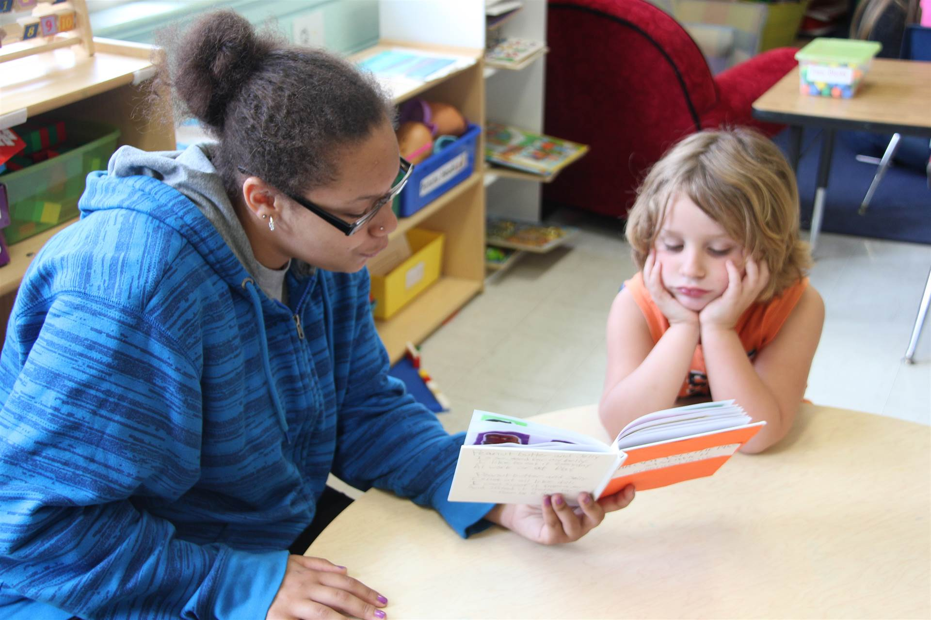 high school girl reads to nursery school student