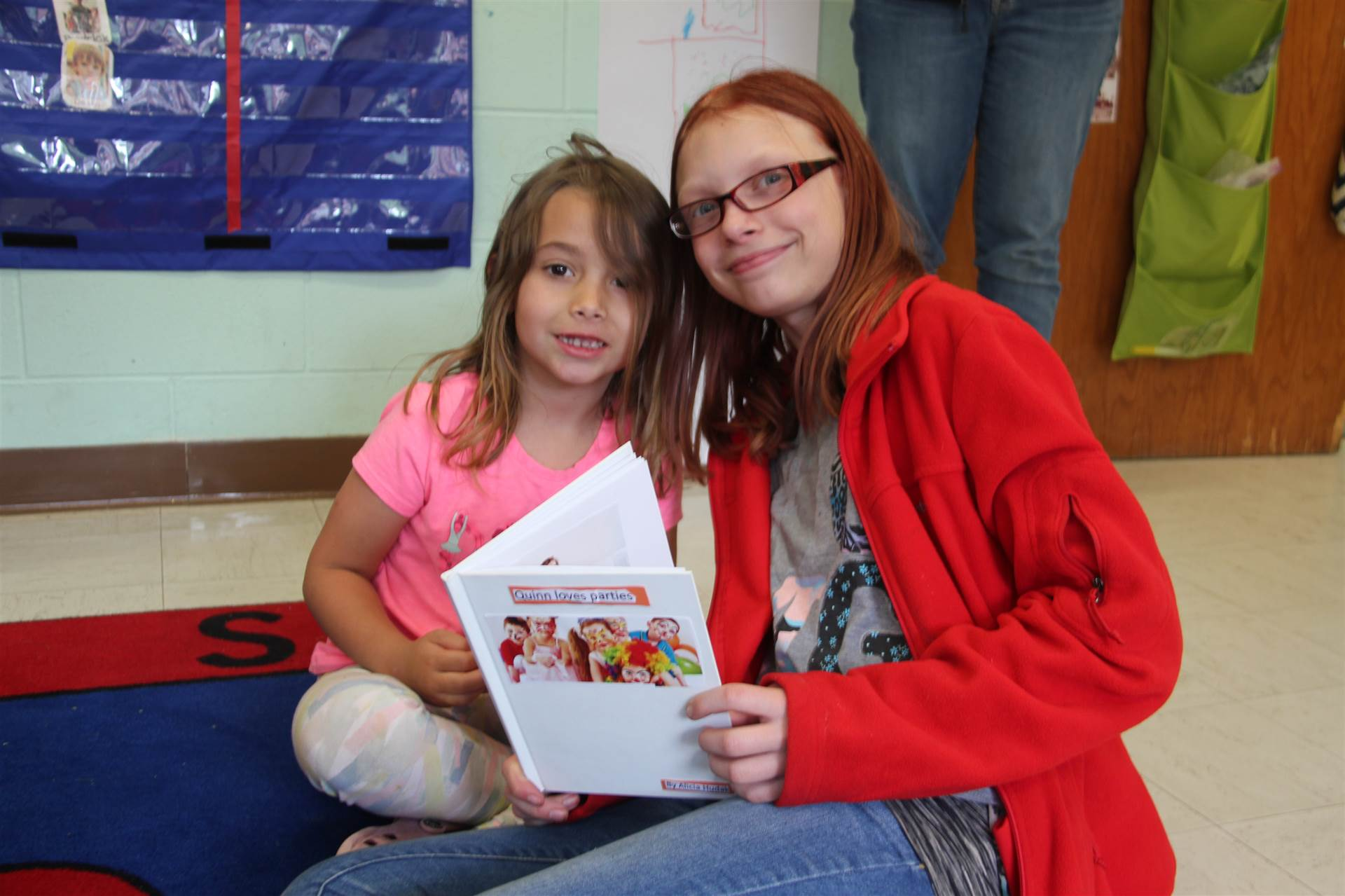 high school student and nursery school student smile holding book