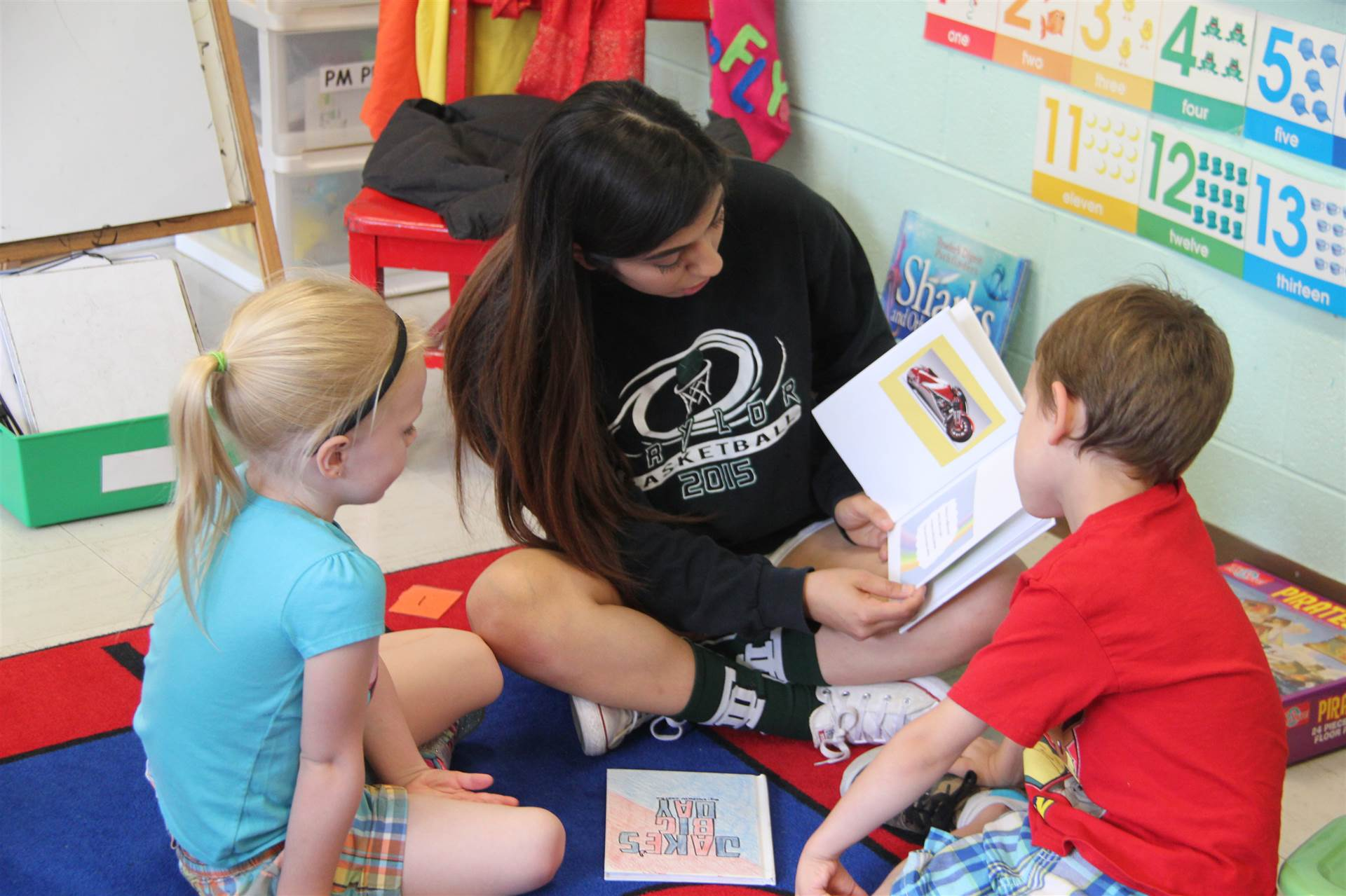 high school student reads to nursery school boy and girl