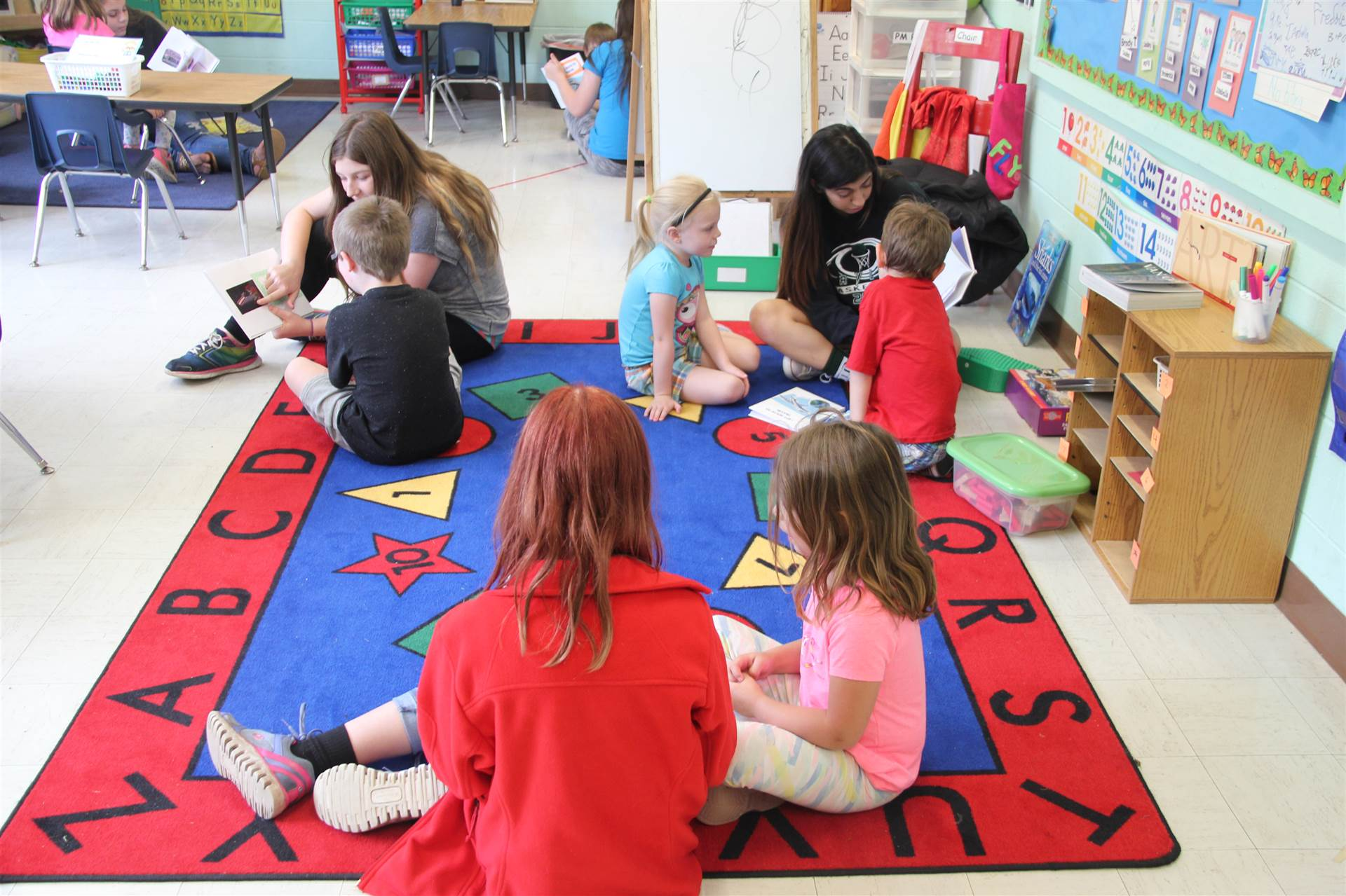 high school child psychology class students read to nursery school students