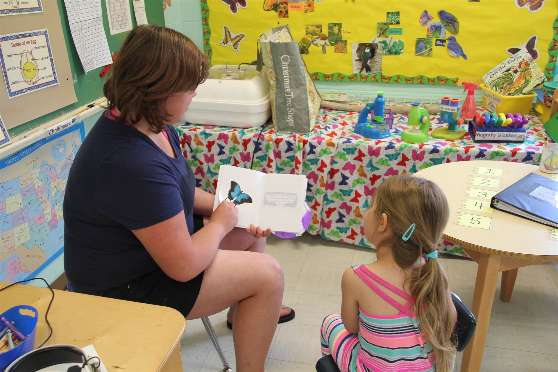 high school girl reads book to nursery school girl