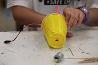 close up of hands working on robot for c v summer steam program