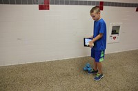 boy controls dash robot using ipad in hallway