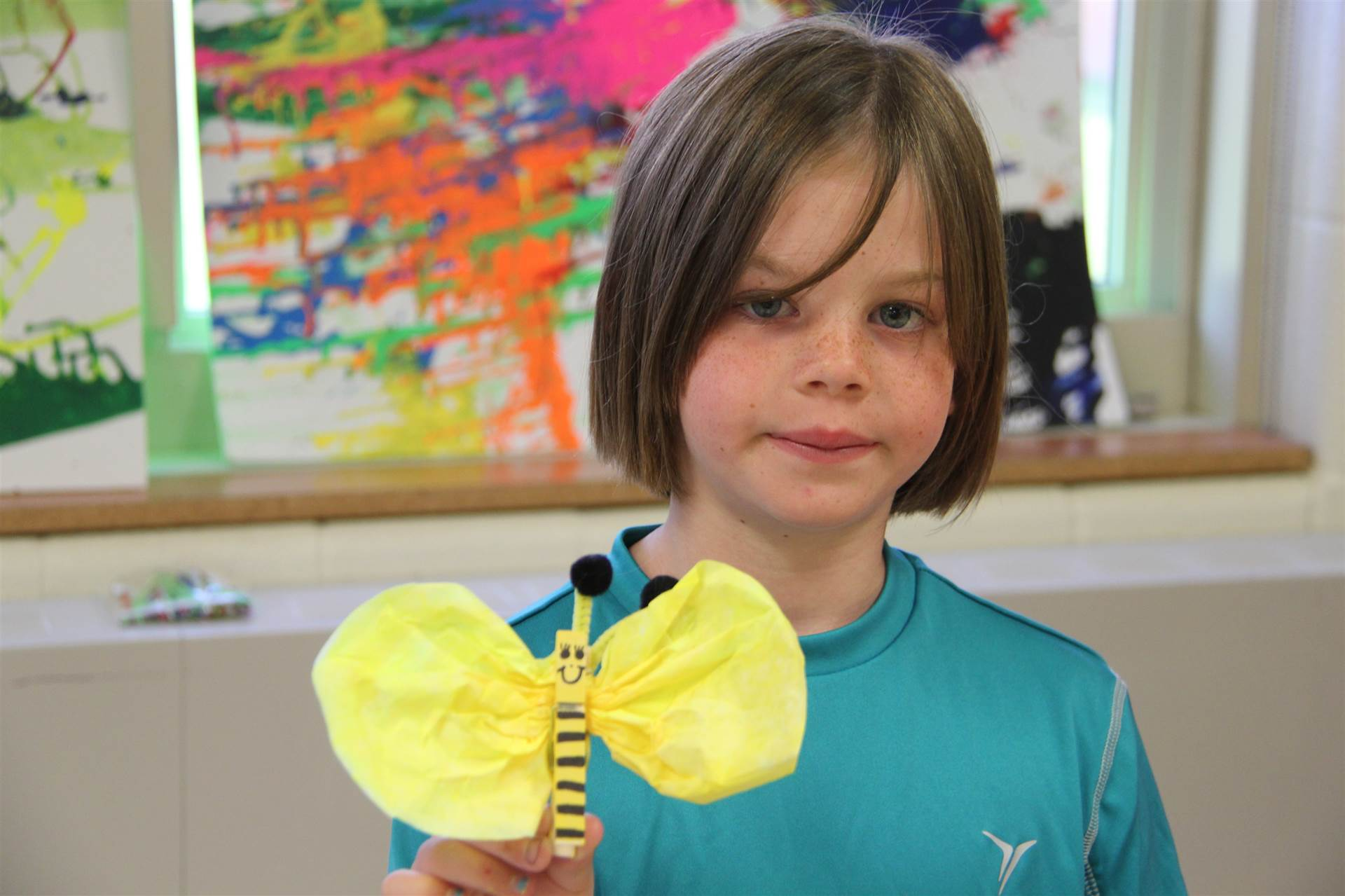 girl smiles with her bee artwork