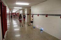 students play with dash robots in the hallway