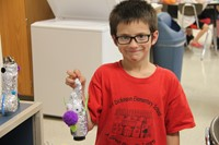 boy smiles with recycled robot project