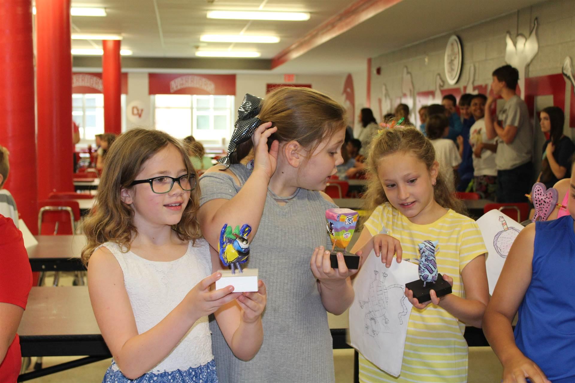 three girls hold their new monster 3 d sculptures
