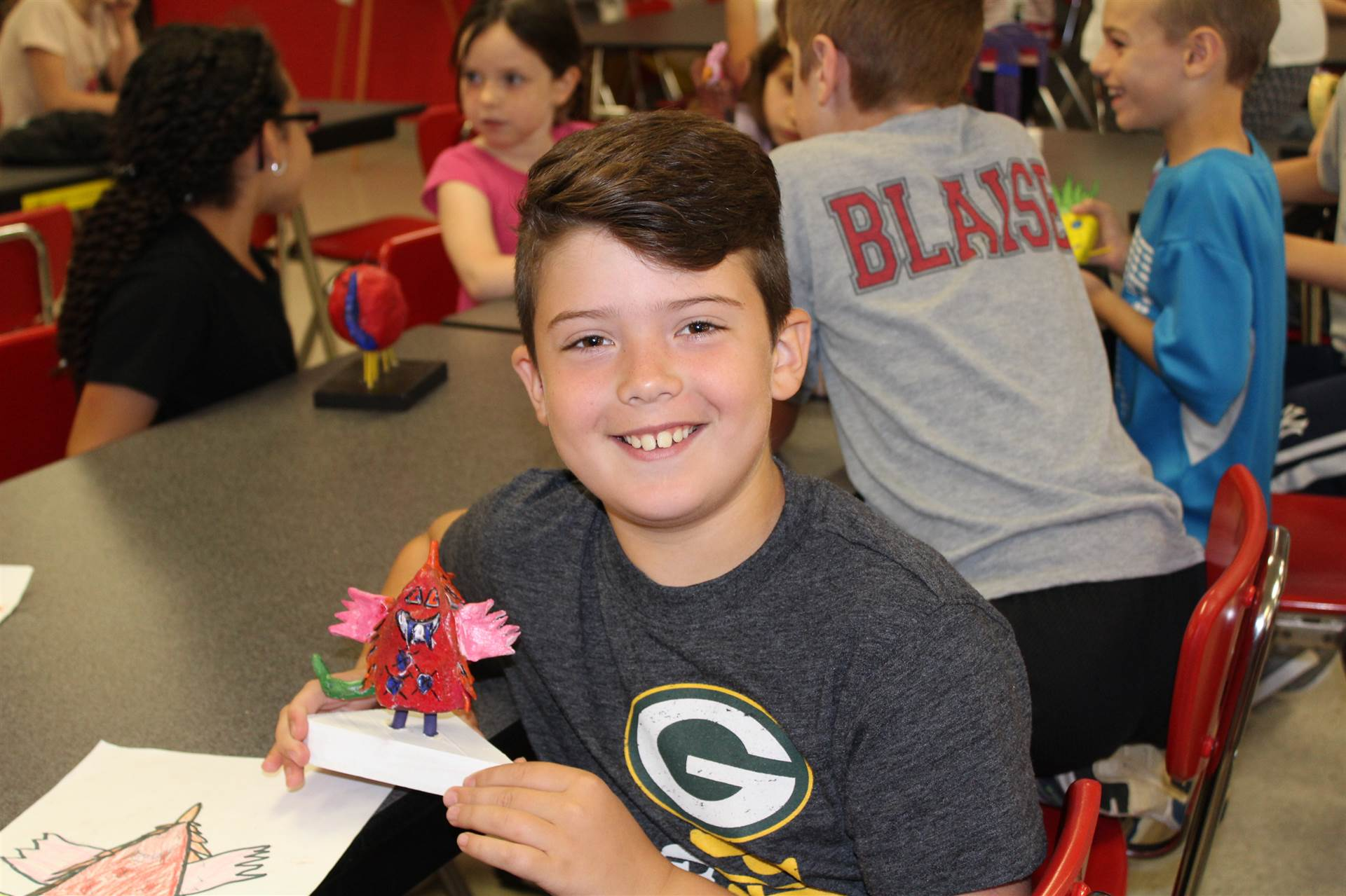 third grade boy smiles sitting while holding new 3 d monster sculpture