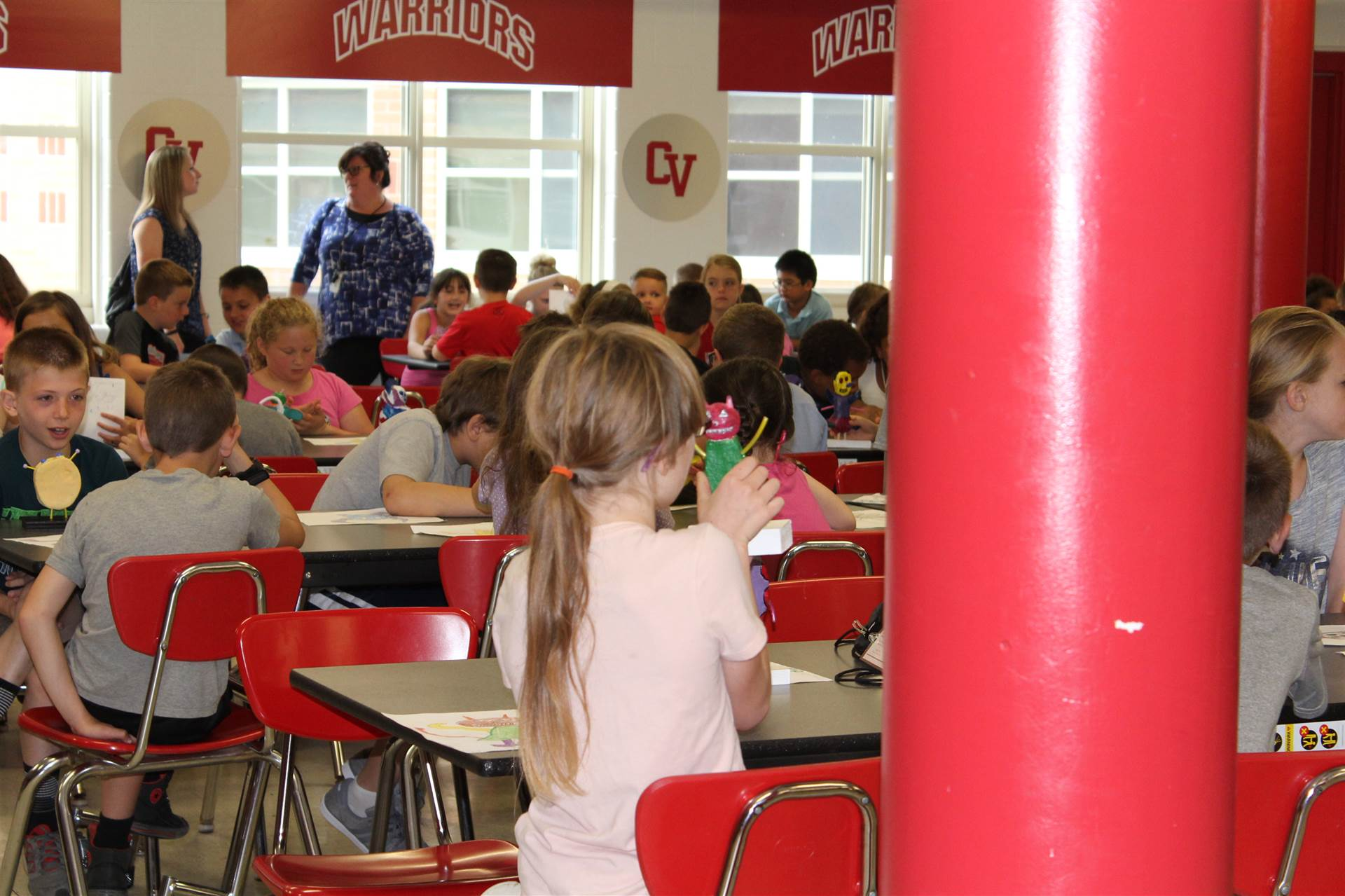 students sit in cafeteria seats with their monster mash reveal creations