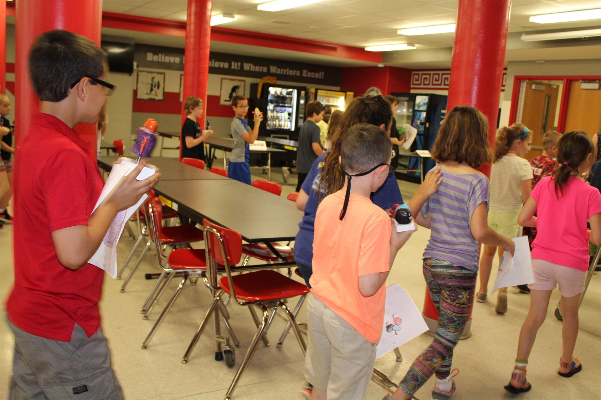 students exit the cafeteria holding 3 d sculptures