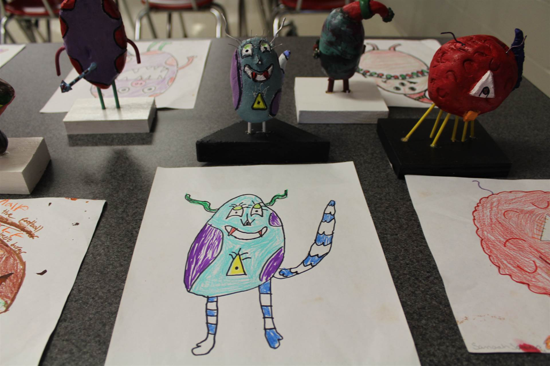 monster 3 d sculpture next to drawn picture 75.