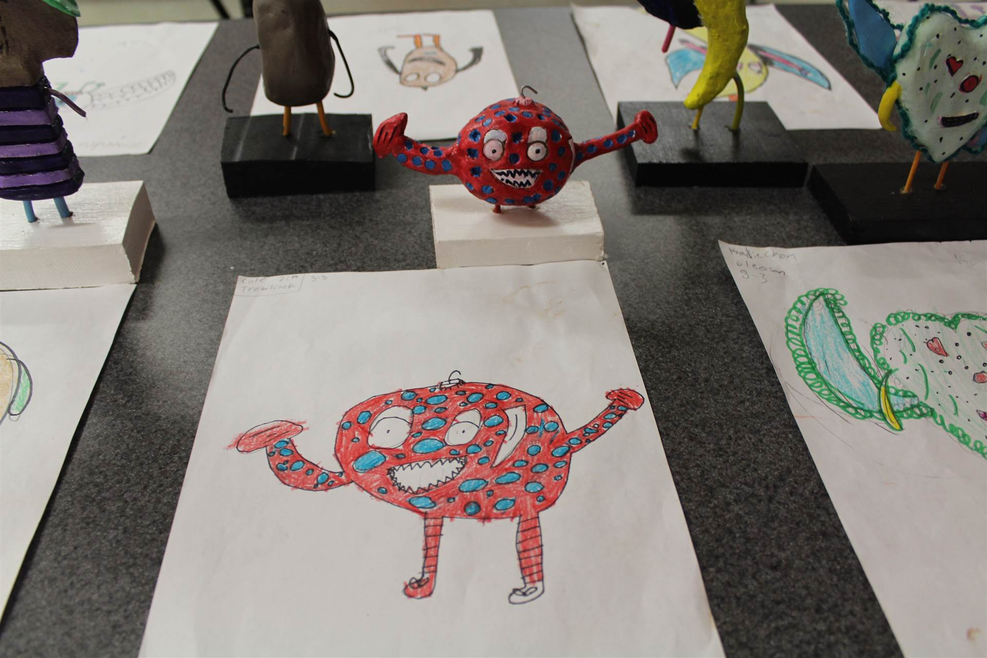 monster 3 d sculpture next to drawn picture 59