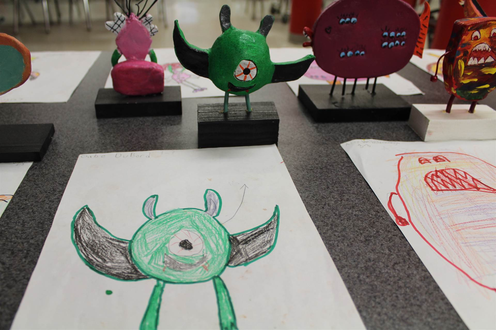 monster 3 d sculpture next to drawn picture 45