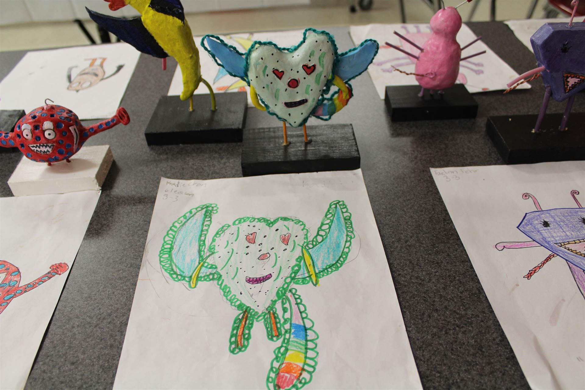 monster 3 d sculpture next to drawn picture 60