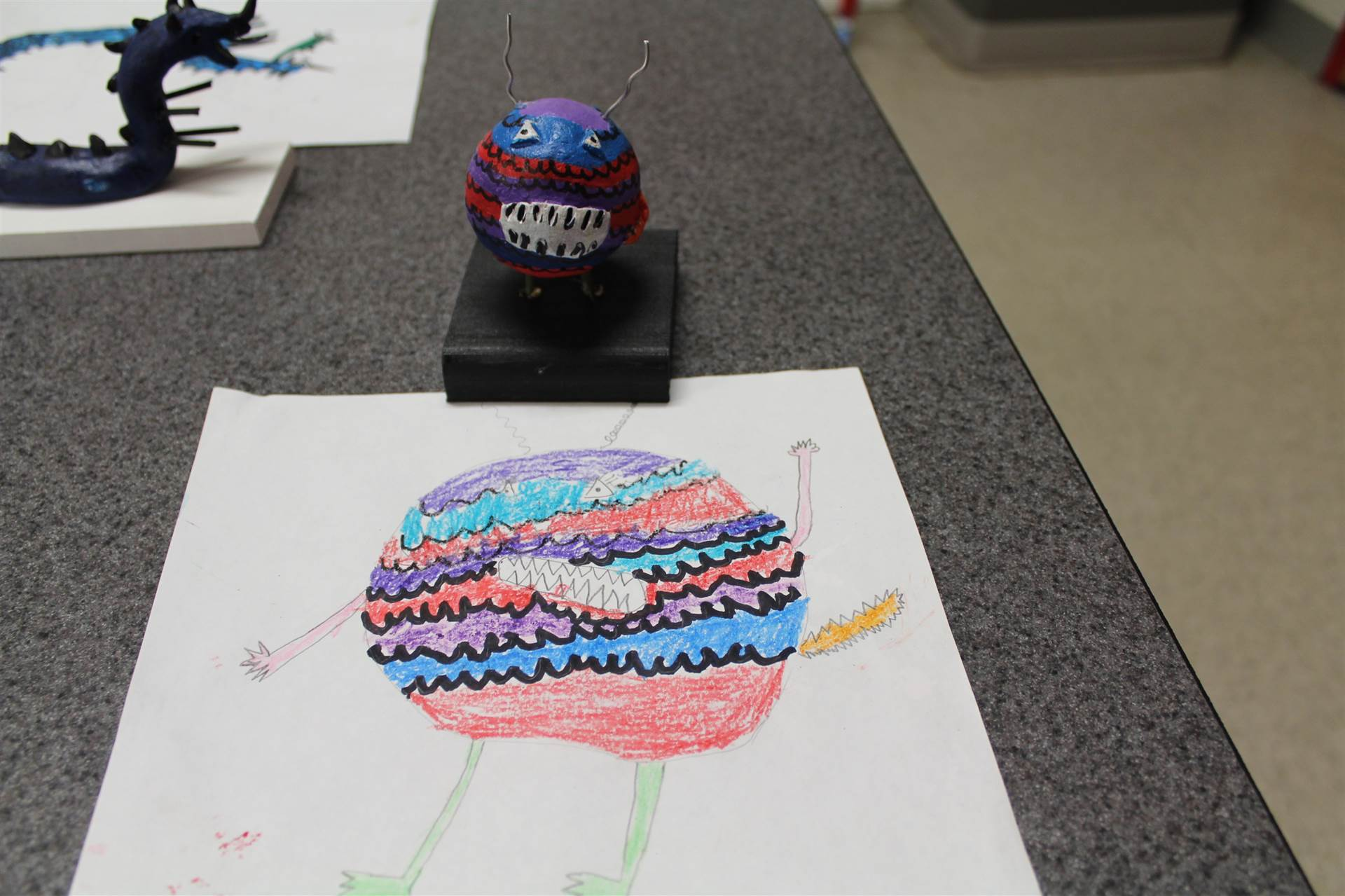 monster 3 d sculpture next to drawn picture 40