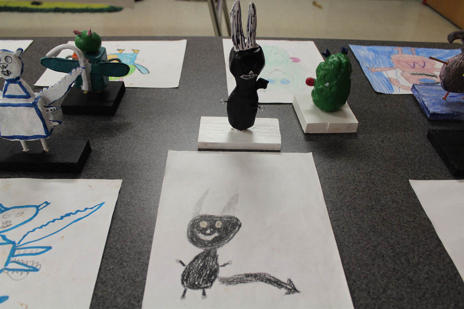 monster 3 d sculpture next to drawn picture 38.