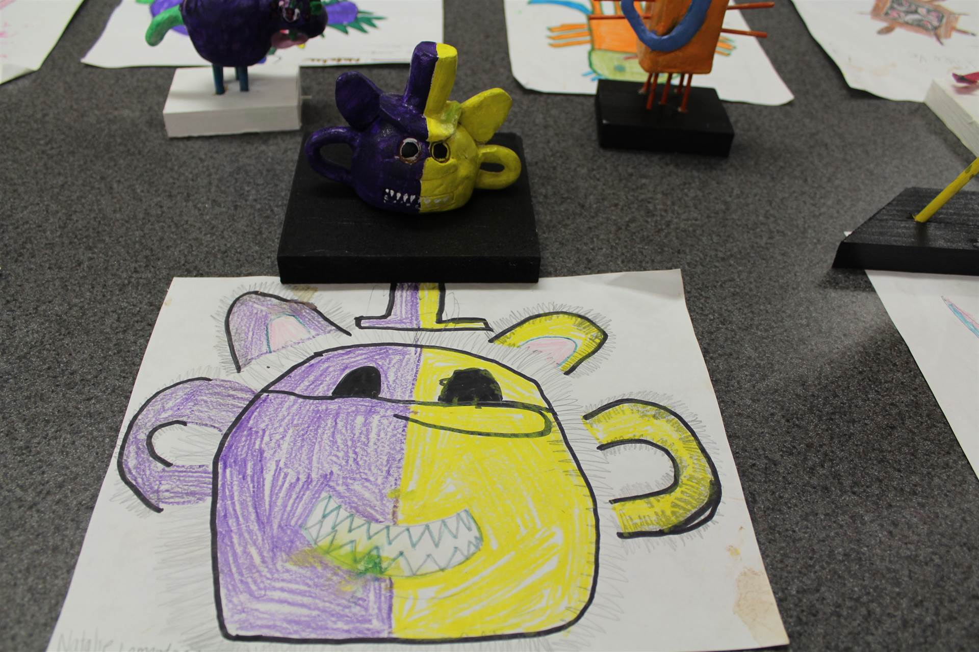 monster 3 d sculpture next to drawn picture 32