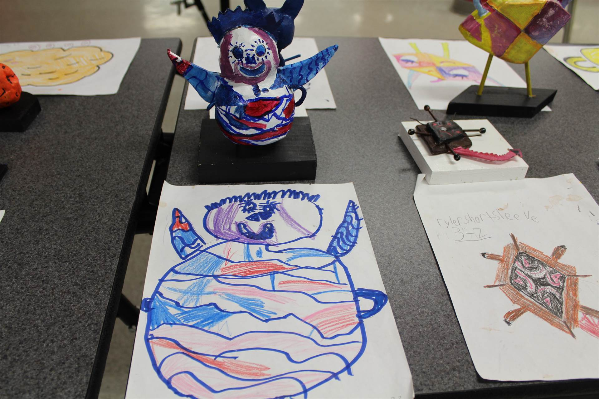 monster 3 d sculpture next to drawn picture 24