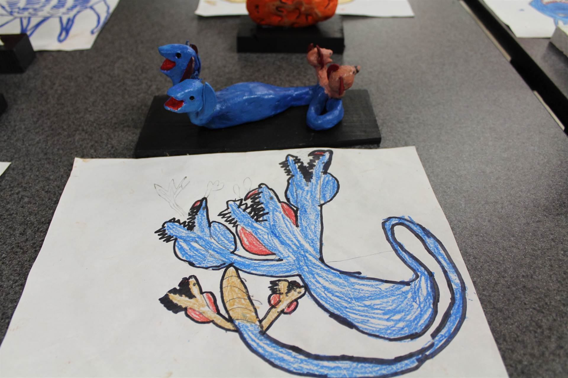monster 3 d sculpture next to drawn picture 23