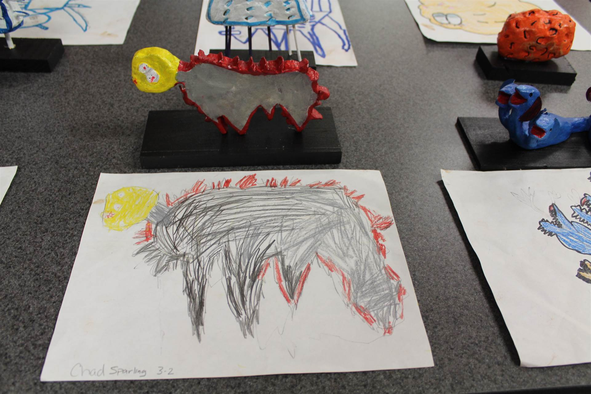 monster 3 d sculpture next to drawn picture 22