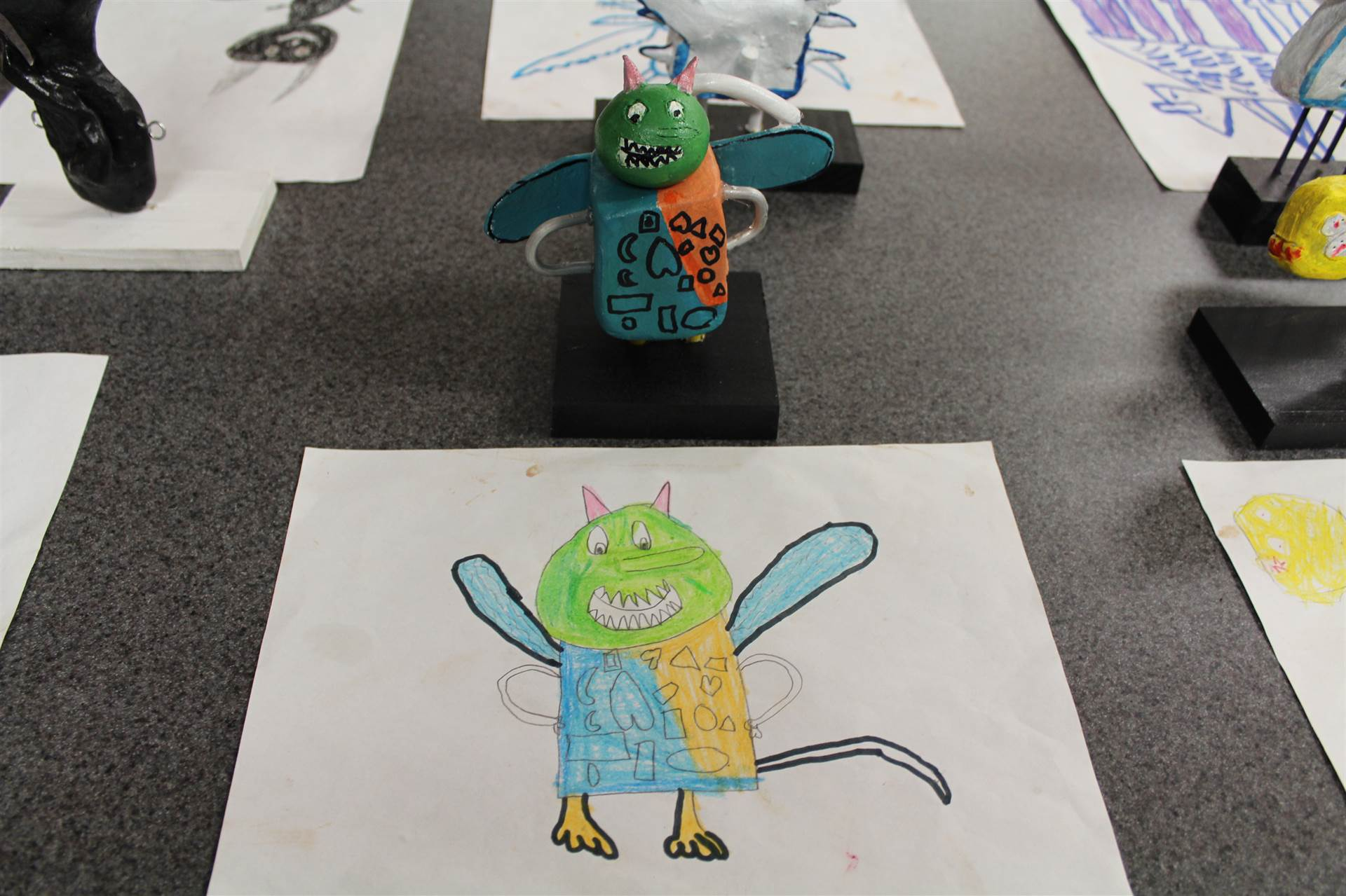 monster 3 d sculpture next to drawn picture 21