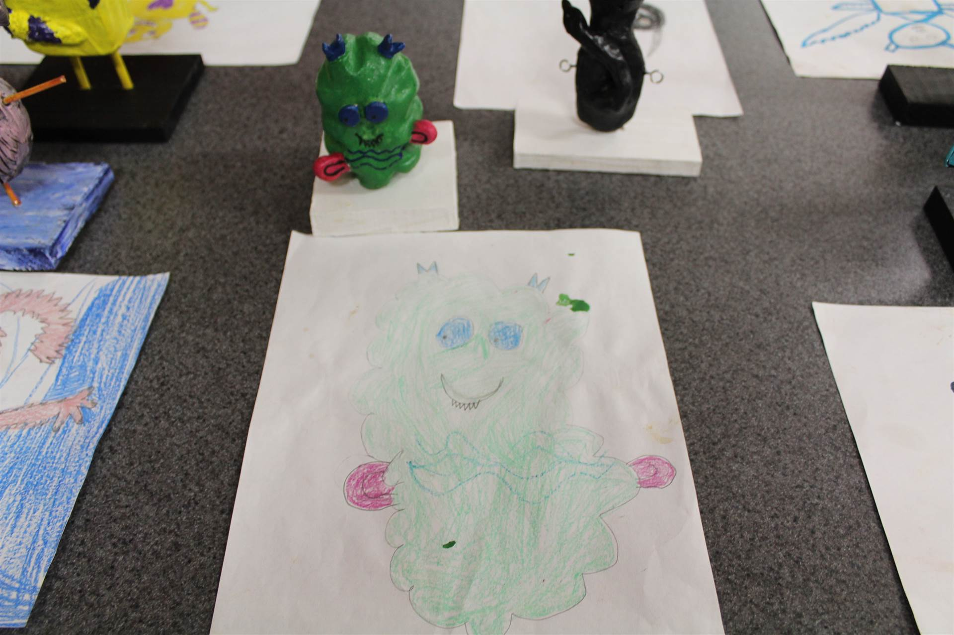 monster 3 d sculpture next to drawn picture 20.