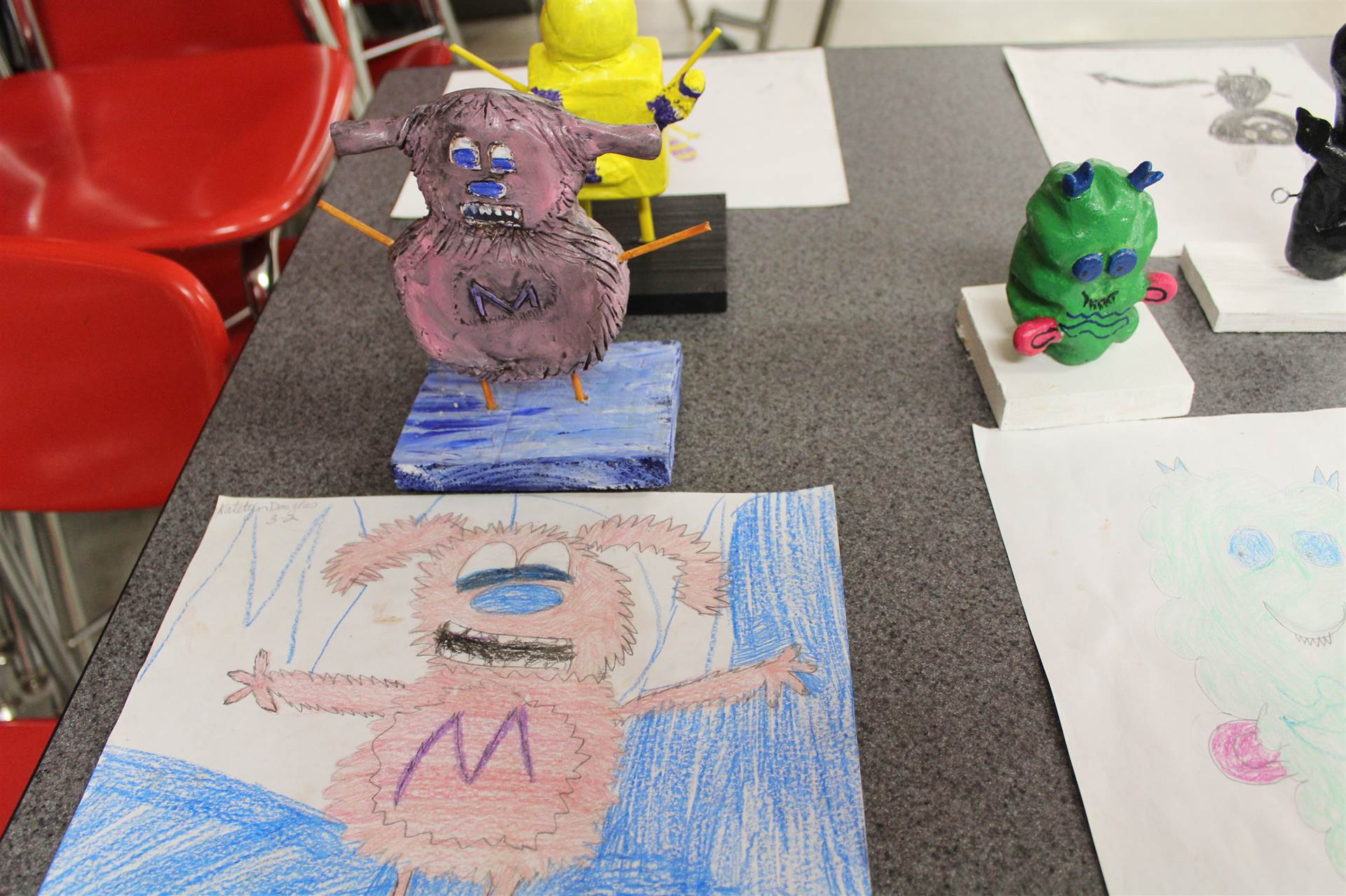 monster 3 d sculpture next to drawn picture 19.