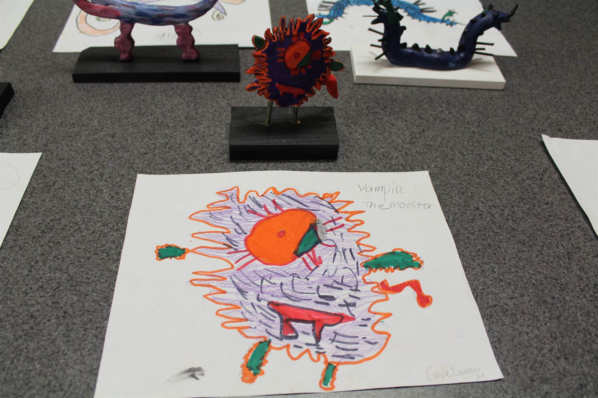 monster 3 d sculpture next to drawn picture 18
